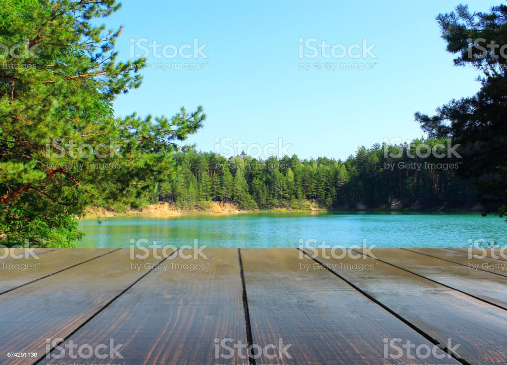 wooden boards near the forest and lake stock photo