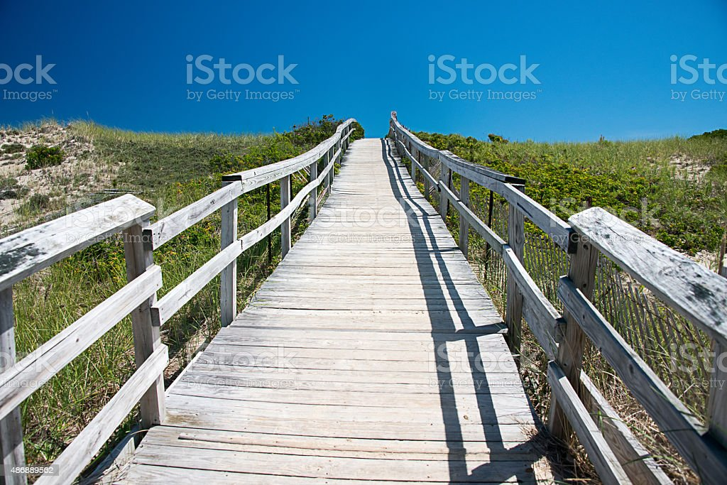 Wooden boardwalk disappears into the distance over sand dunes stock photo