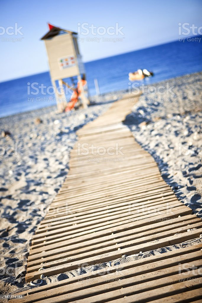 Wooden boardwalk towards beach stock photo
