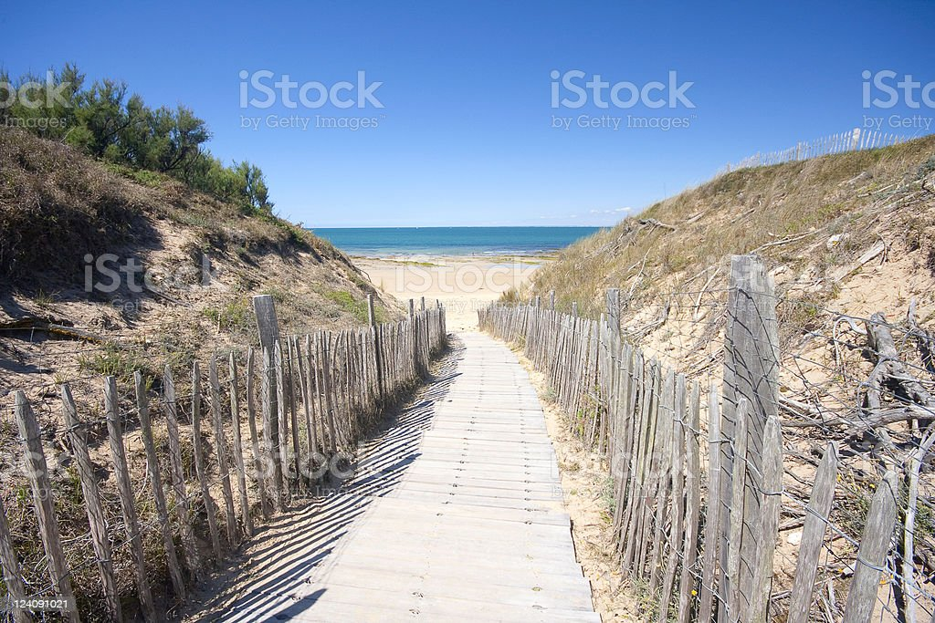 Wooden boardwalk with fences leading to the beach stock photo