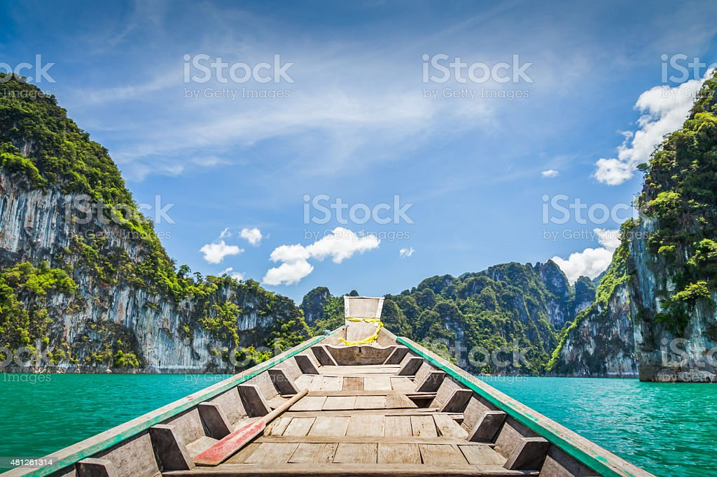 wooden boat in blue river stock photo
