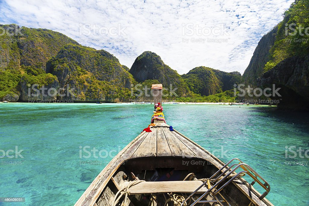 Wooden boat in crystal water on Phi Island, Thailand stock photo
