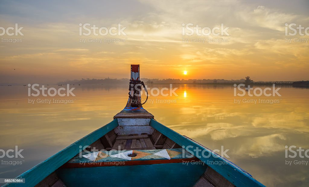 Wooden boat in Ubein Bridge at sunrise, Mandalay, Myanmar stock photo