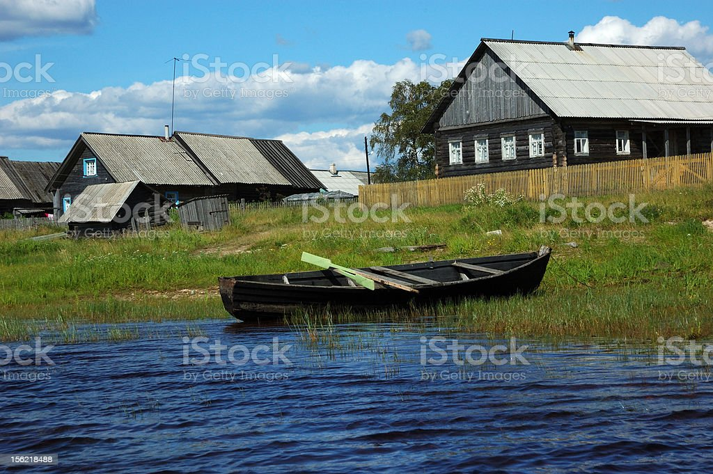 Wooden boat on the lake bank in small village royalty-free stock photo