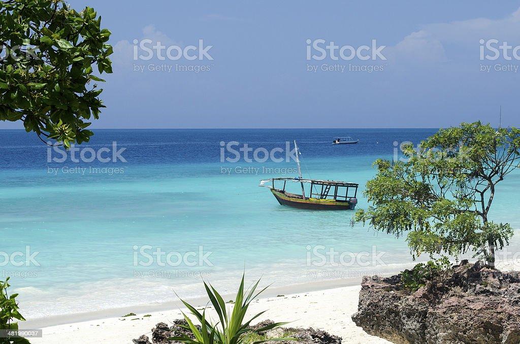 Wooden boat on turquoise water in Zanzibar stock photo