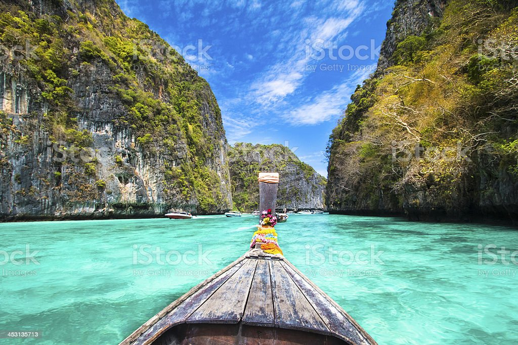 A wooden boat sailing near phi island in Thailand stock photo