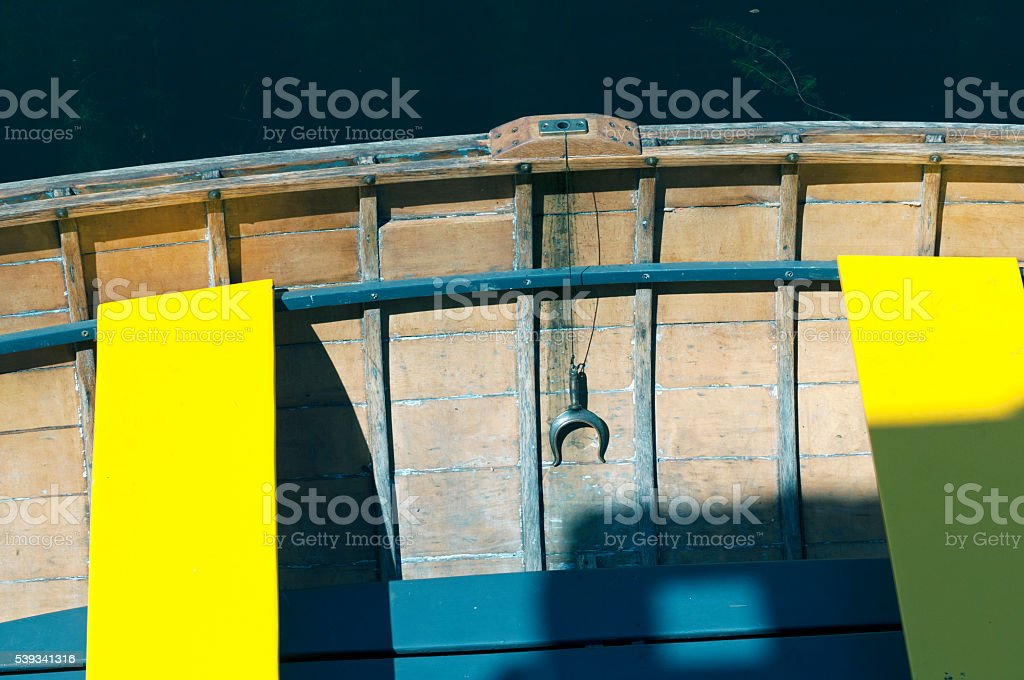 Wooden boat with oarlock and yellow seats on lake stock photo