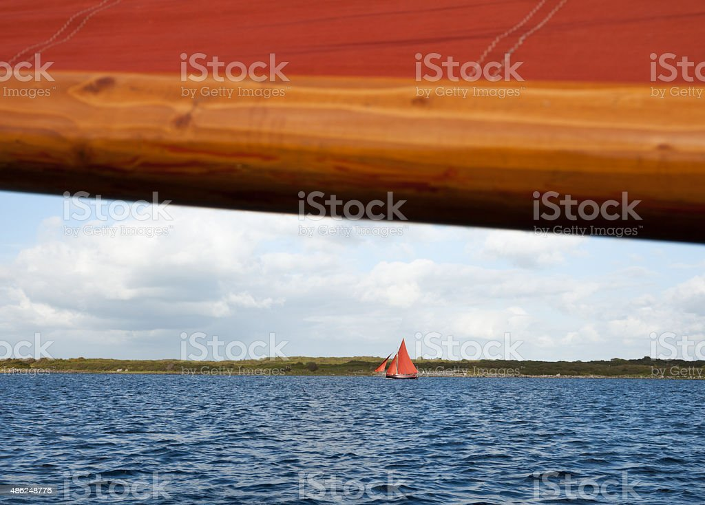 Wooden boat with sail stock photo