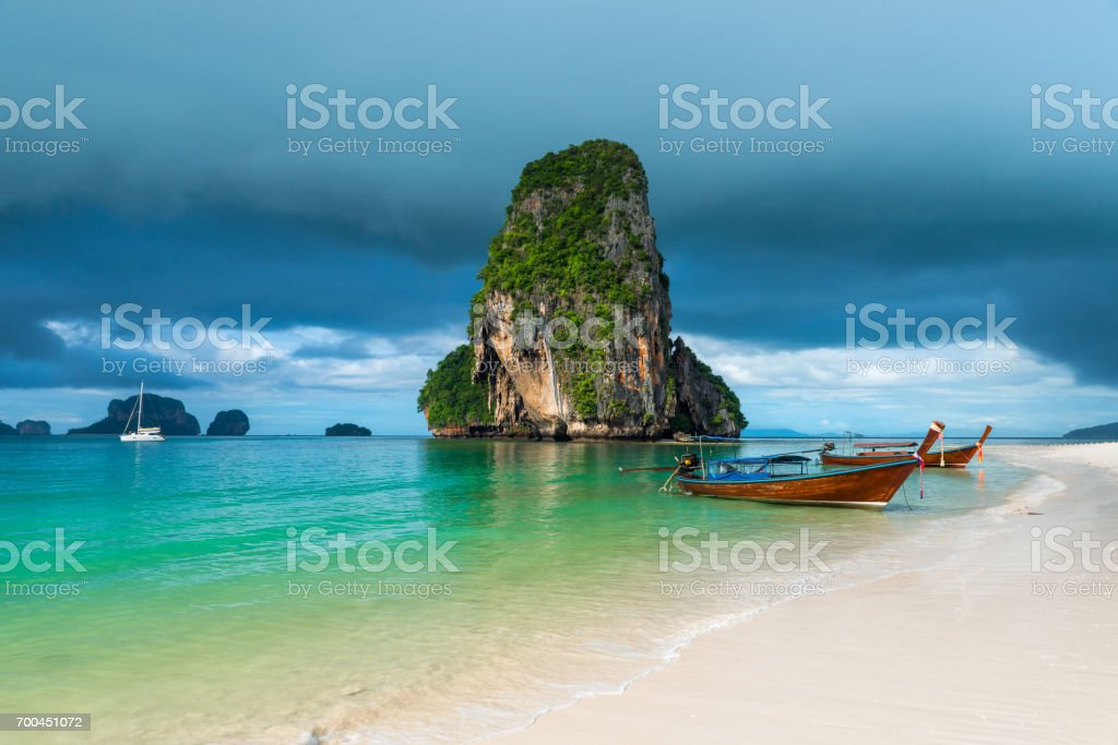 Wooden boats and a high cliff in the sea, Thailand, Phra Nang beach stock photo