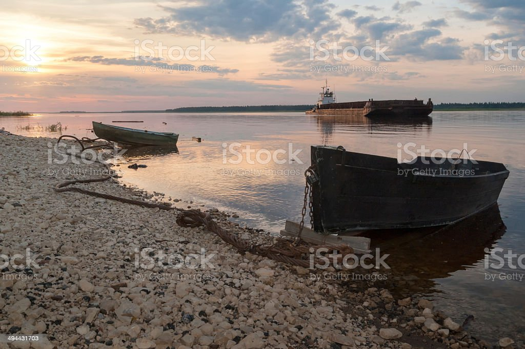 Wooden boats and cargo ship against river panorama at sunset stock photo