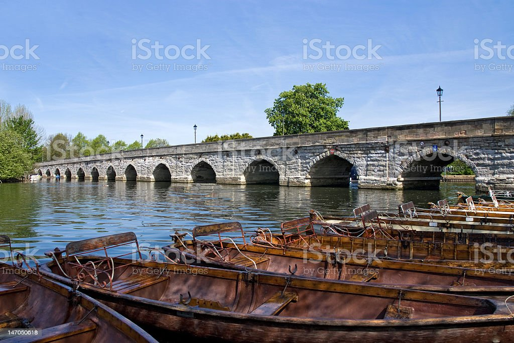 Wooden boats on the river next to stone bridge  stock photo