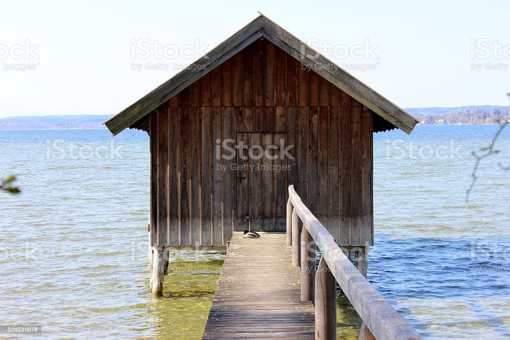 Wooden boatshed on the lake with narrow passage bridge stock photo