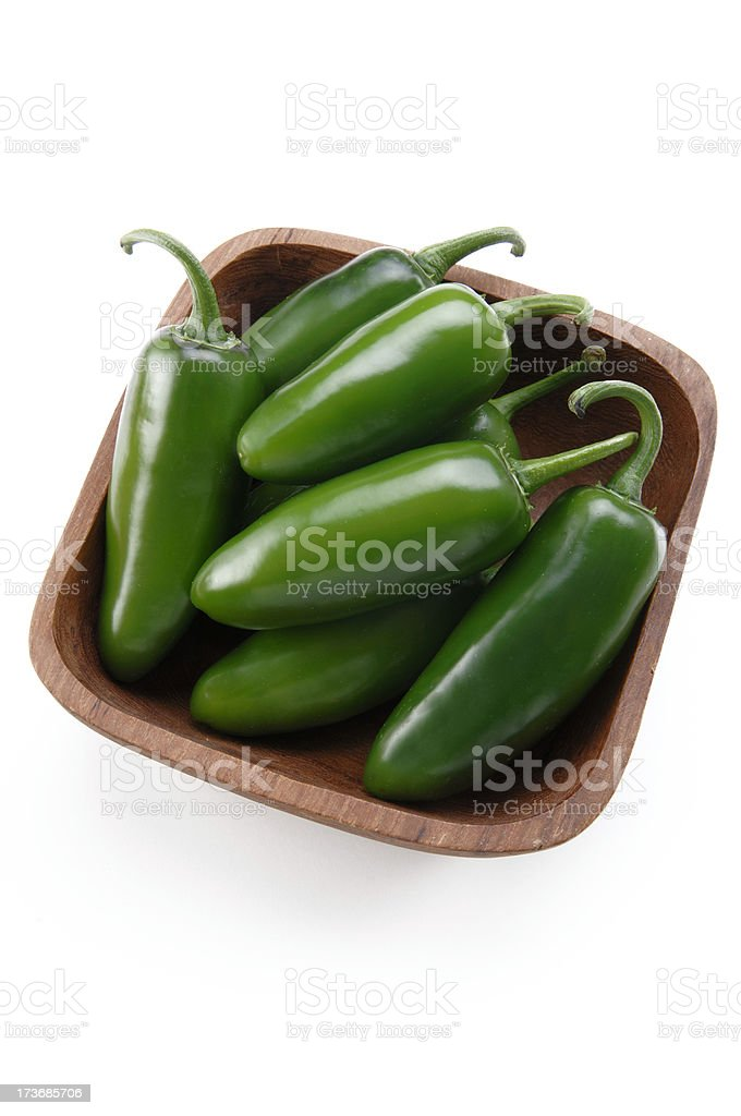 A wooden bowl full of jalapee stock photo