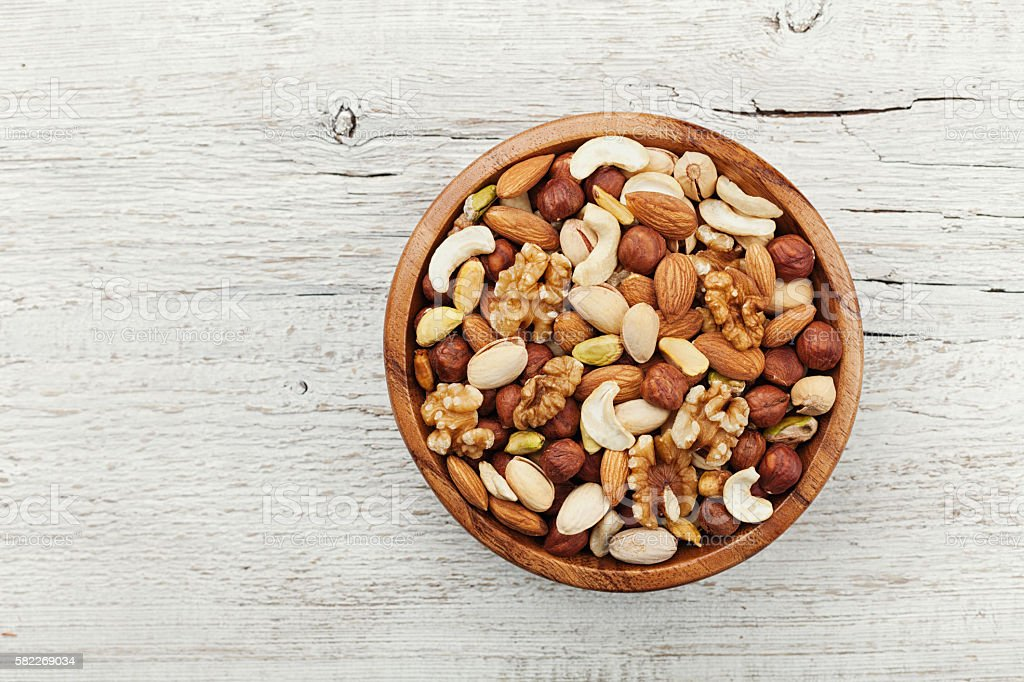 Wooden bowl with nuts. Walnut, pistachios, almonds, hazelnuts. Flat lay. stock photo
