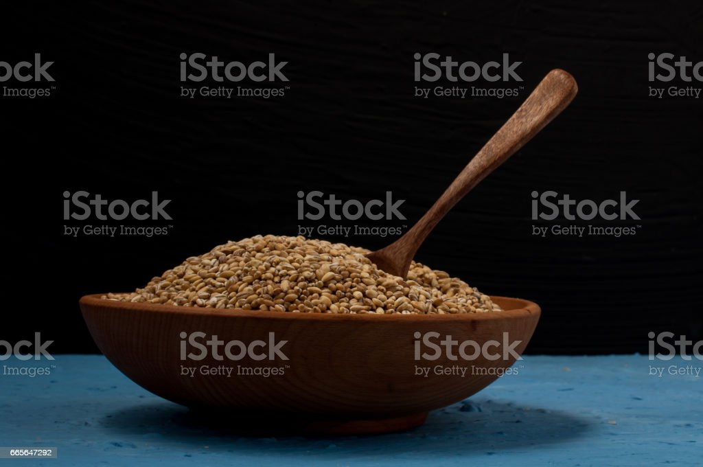 Wooden bowl with pearl barley on blue and black background. Close-up. stock photo