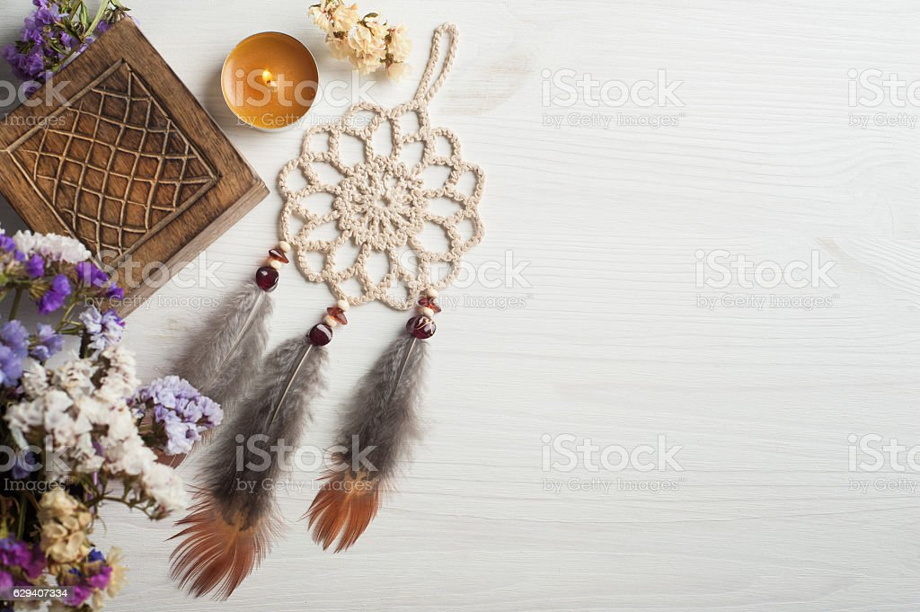 Wooden box and beige dream catcher, lit candle stock photo