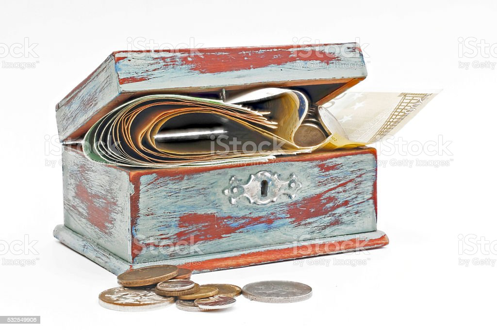 Wooden box filled with banknotes and coins stock photo