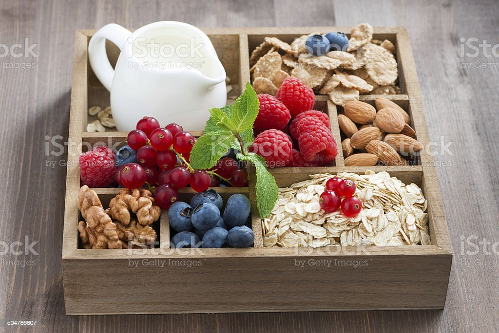 wooden box with breakfast - oatmeal, granola, nuts, berries stock photo