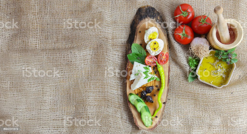 Wooden Breakfast Plate with Tomato, Cheese, Egg, Olive, Green Pepper, Garlic and Olive Oil stock photo