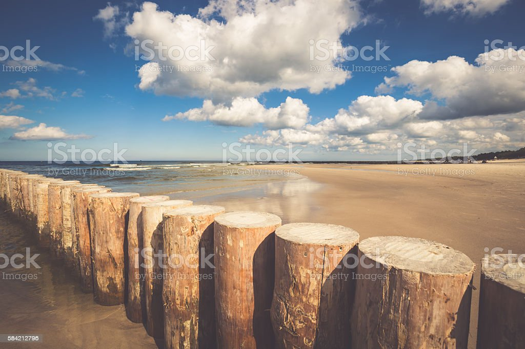 Wooden breakwaters on sandy Leba beach in late afternoon, Baltic stock photo