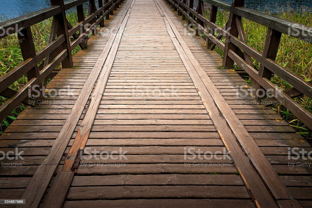 Wooden bridge across the river stock photo