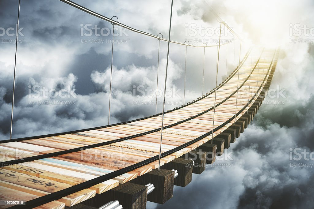 Wooden bridge in the clouds going to sunlight, concept stock photo