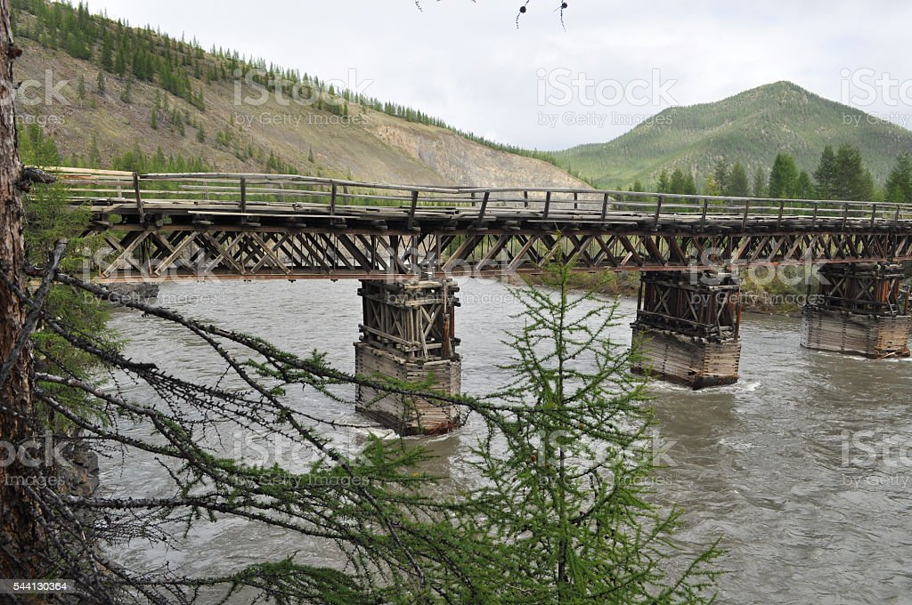 Wooden bridge in Yakutia across the mountain river. stock photo