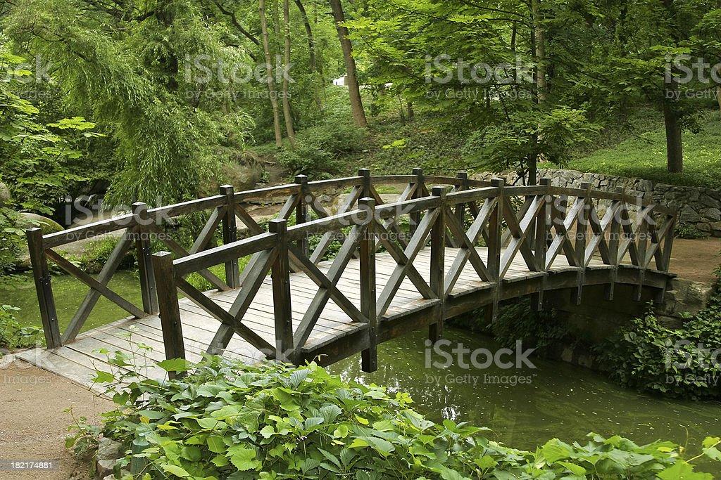 Wooden bridge over a stream through a landscaped garden royalty-free stock photo