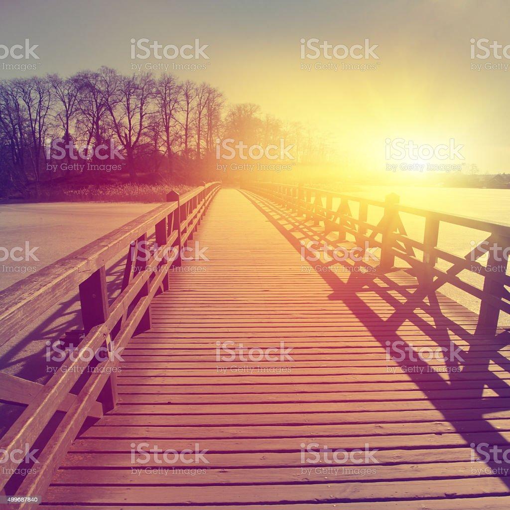 Wooden bridge over frozen river. stock photo