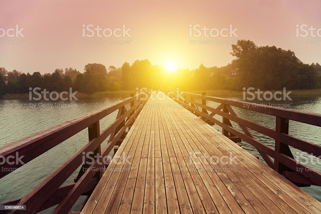 Wooden bridge over lake in early misty morning stock photo