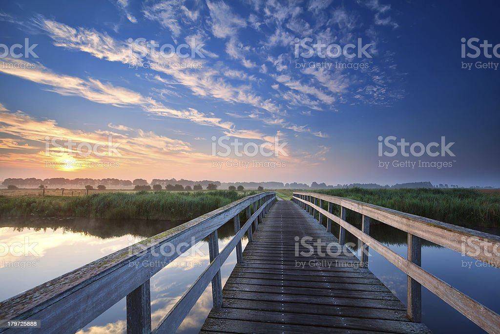 wooden bridge over river at sunrise royalty-free stock photo