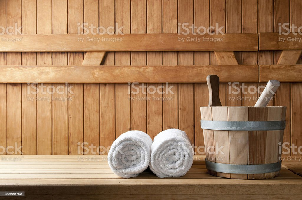 Wooden bucket and white rolled towels in a sauna stock photo