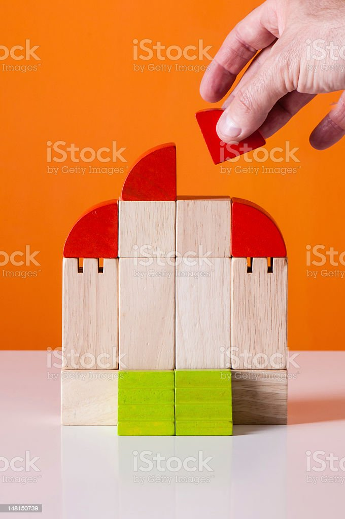 Wooden building blocks: hand place a brick stock photo