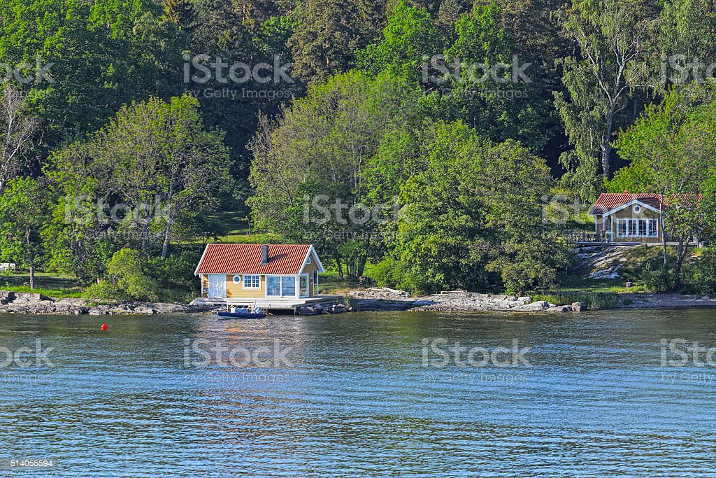 Wooden cabin on rocky shore stock photo