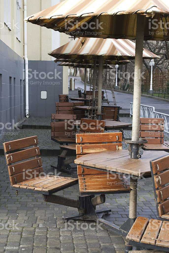Wooden cafe chairs, tables and umbrellas stock photo