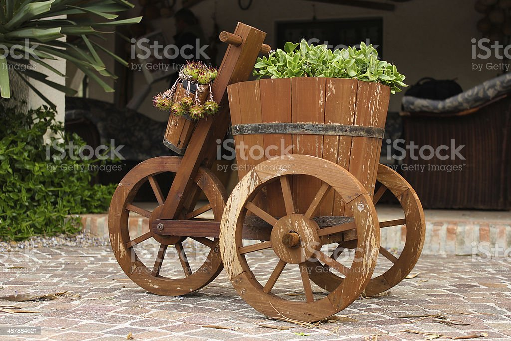 Wooden cart with vase and flowers stock photo