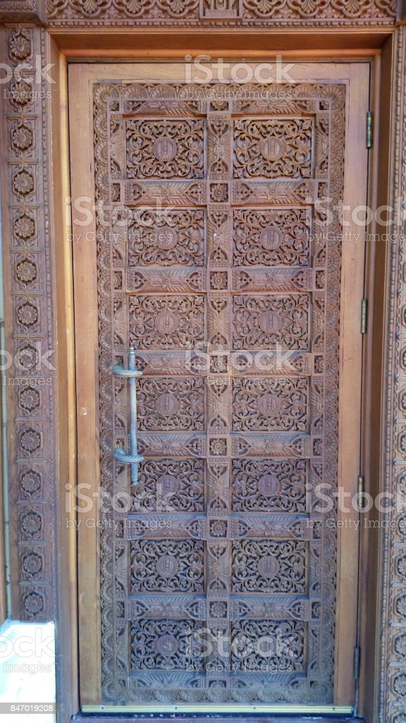 A wooden carved door of BAPS Swaminarayan Temple stock photo