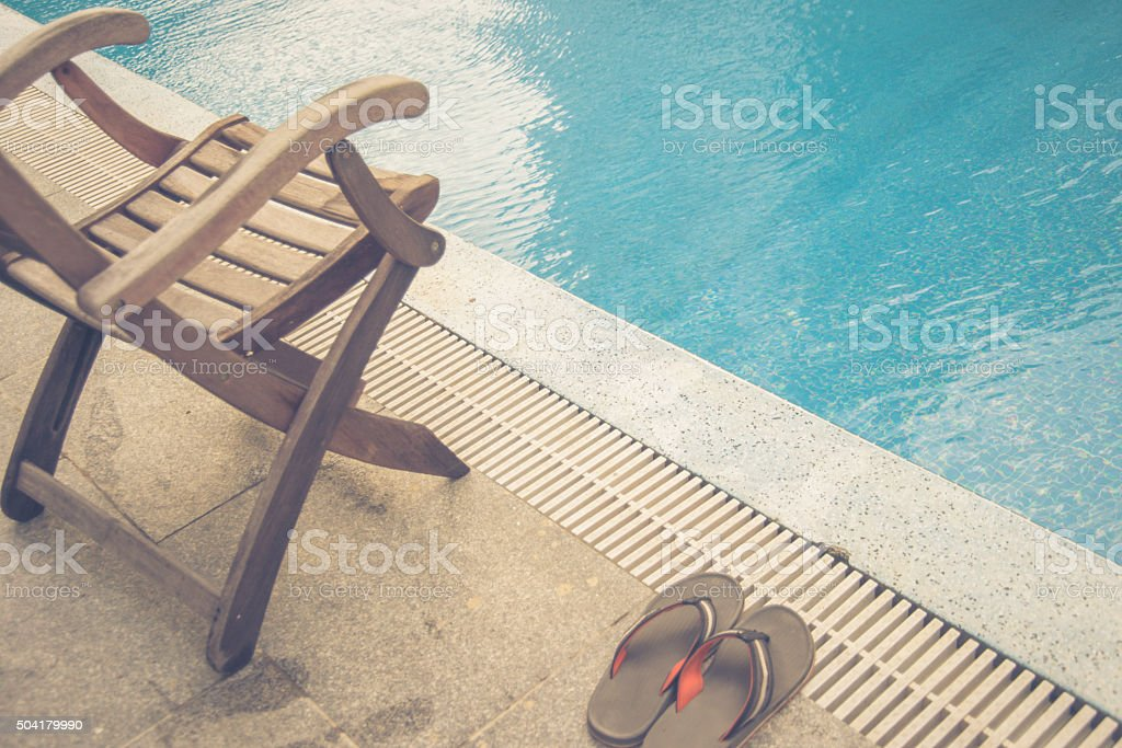 Wooden chair and slippers beside swimming pool stock photo