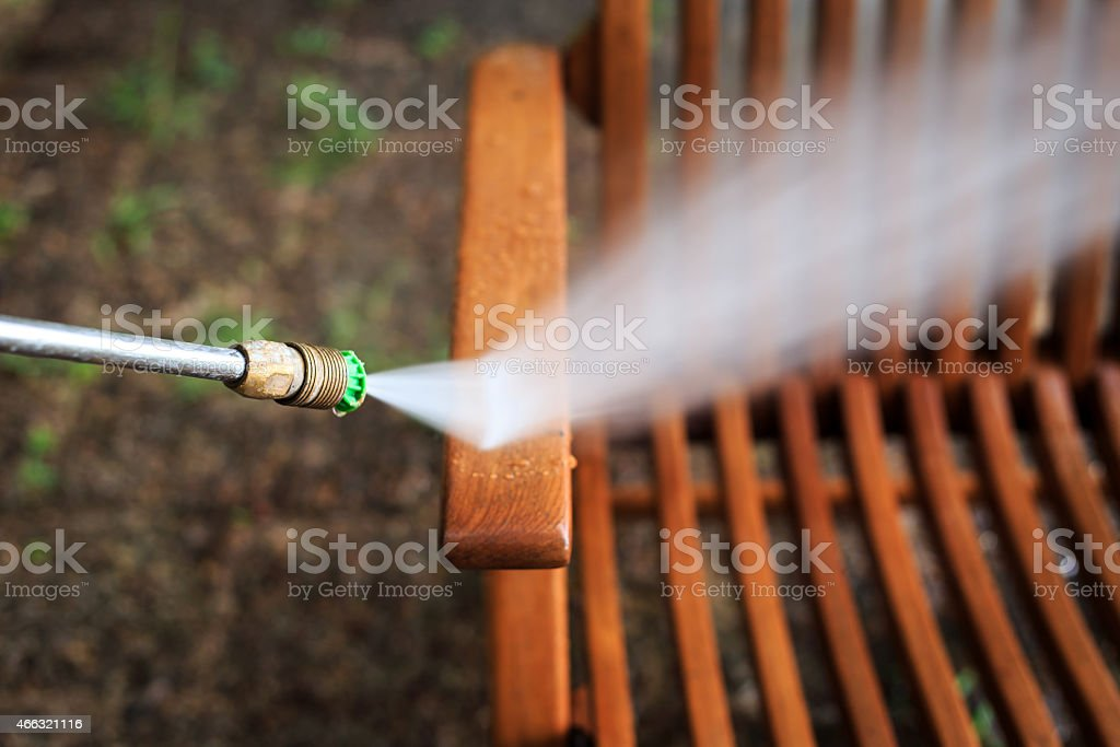 Wooden chair cleaning with high pressure water jet stock photo