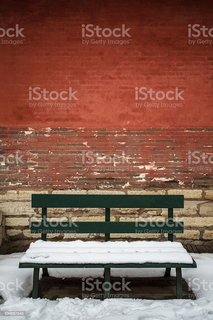 wooden chair covered with snow,under red wall stock photo