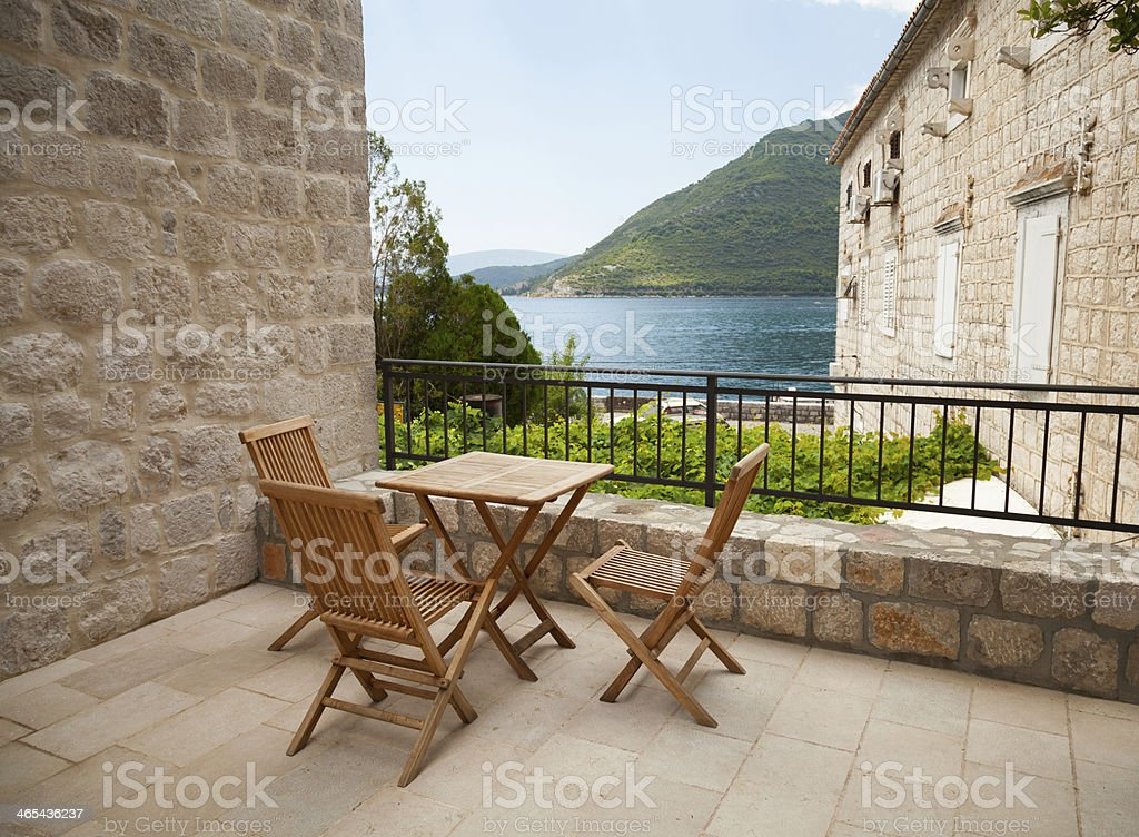 Wooden chairs and table on open seaside terrace stock photo