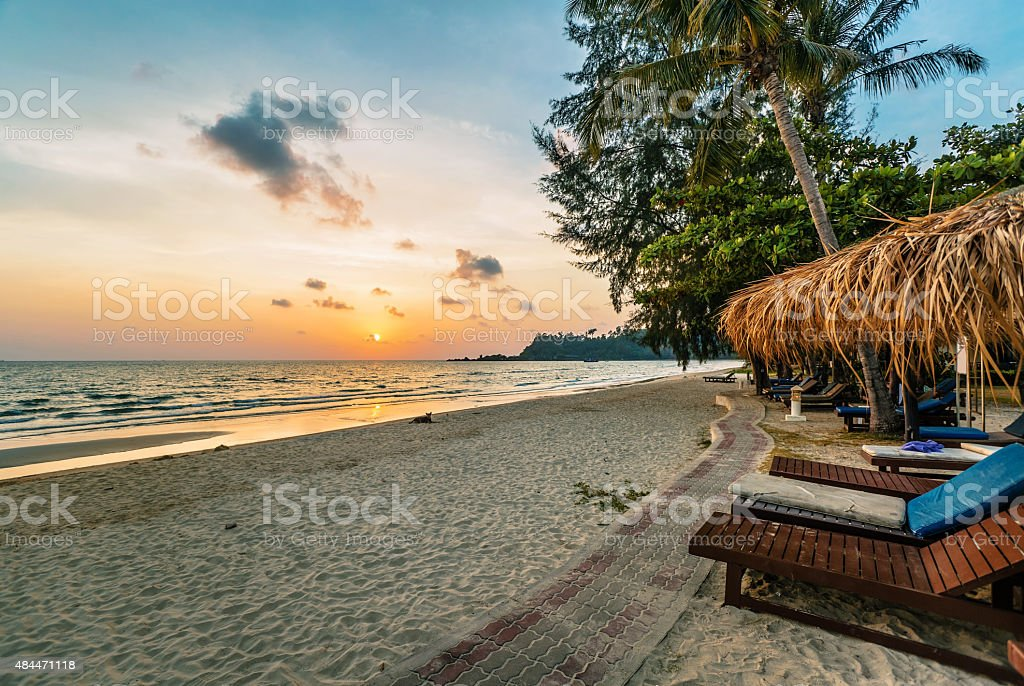 Wooden chairs and umbrellas on sand beach stock photo