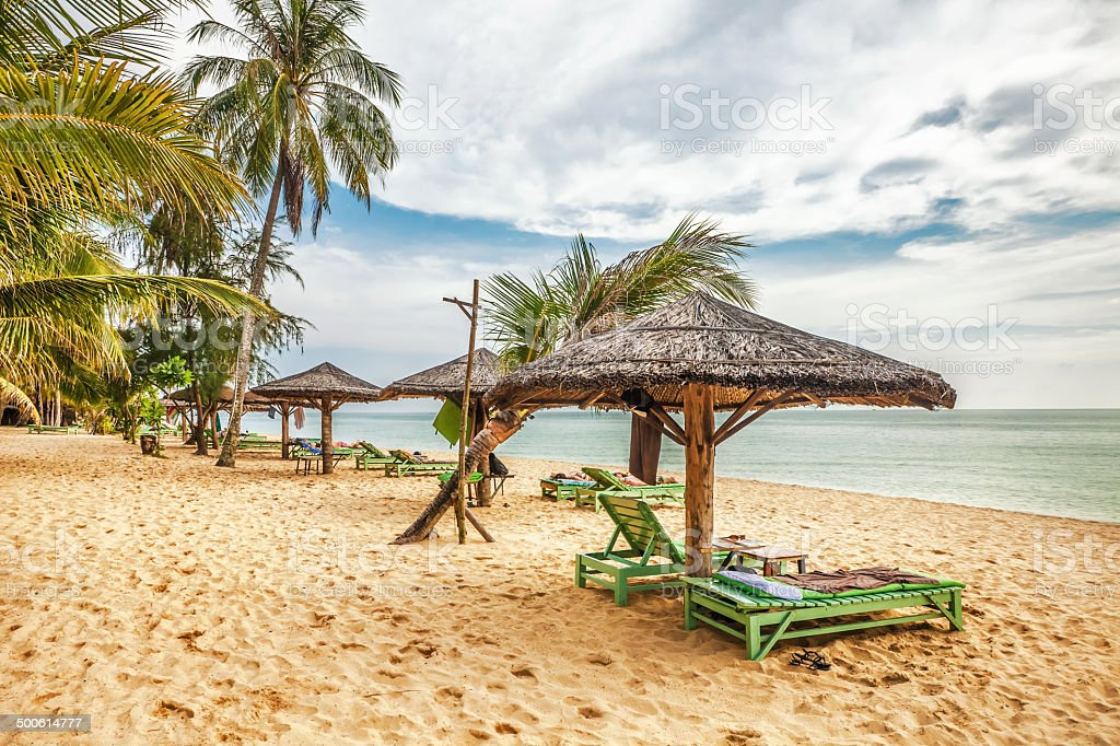 Wooden chairs and umbrellas on white sand beach stock photo