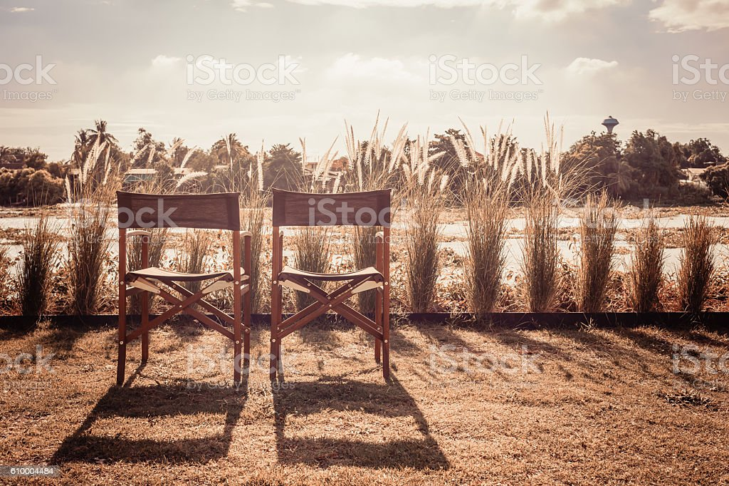 wooden chairs with chair shadow in  backyard near the river stock photo