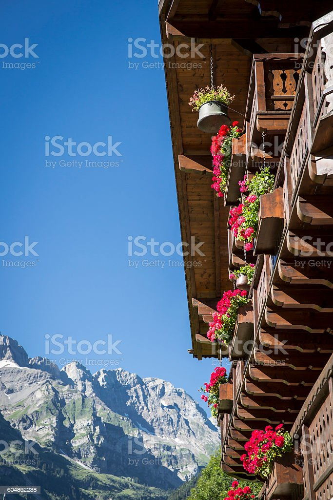 wooden chalet with mountain and blue sky in the background stock photo