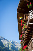 wooden chalet with mountain and blue sky in the background