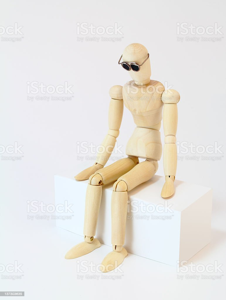 Wooden character sitting in deep thought stock photo
