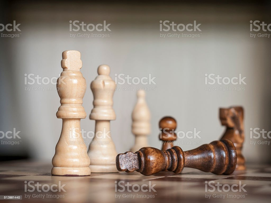 Wooden Chess Figures With The Black King Surrendering stock photo