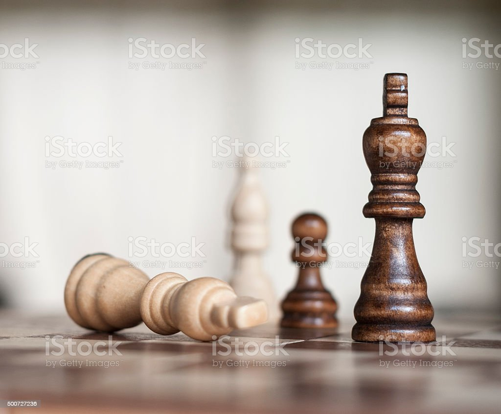 Wooden Chess Figures With The White King Surrendering stock photo