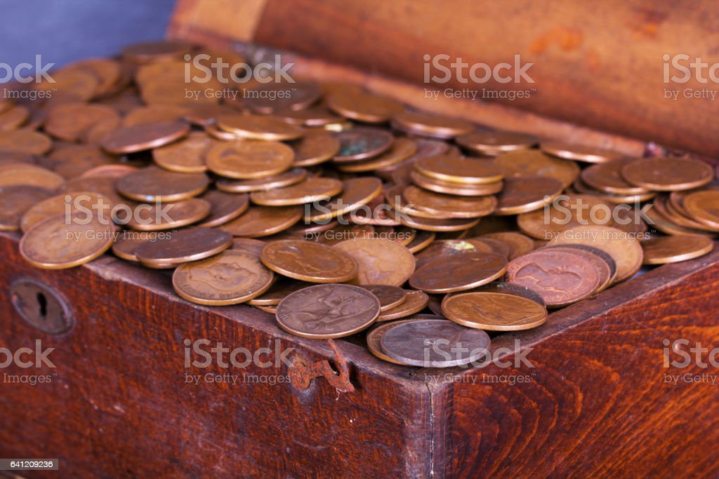 Wooden chest filled with old copper coins stock photo